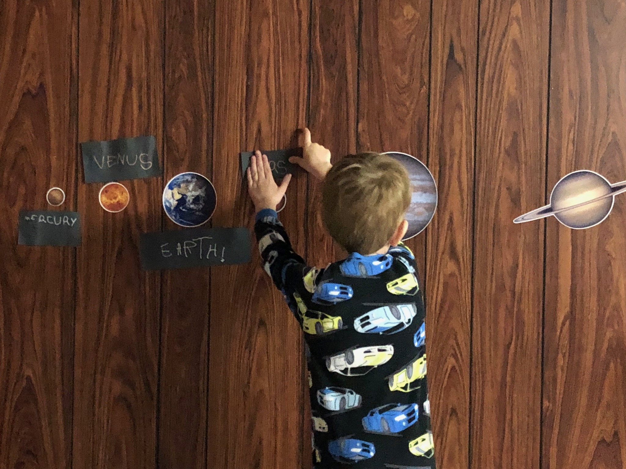 A young boy is sticking a black label for Mars up on a wall. Planet wall stickers and labels can be seen for Mercury, Venus and Earth