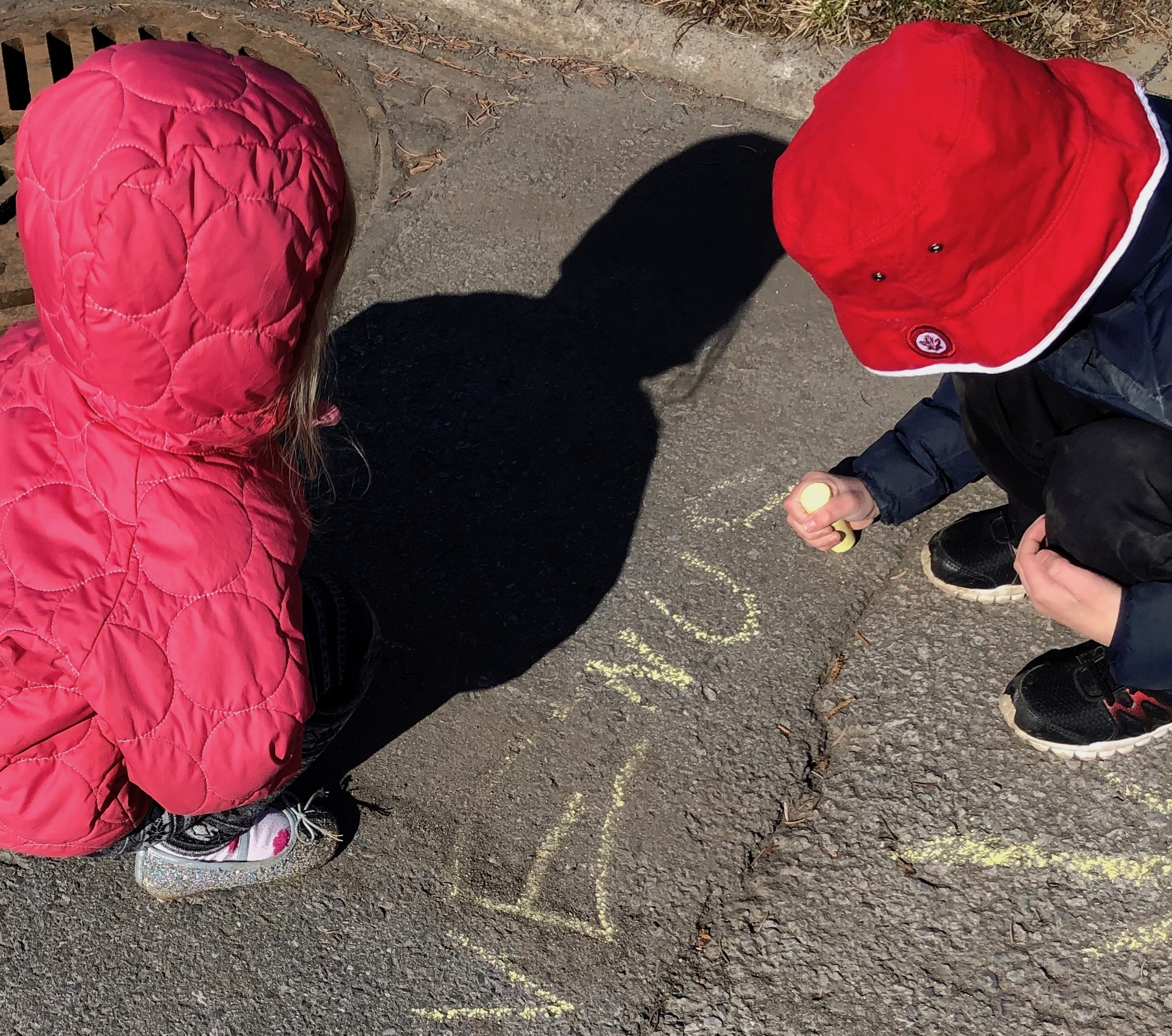 A young girl and a young boy look at the ground as the boy writes Venus in chalk. The girl's shadow is seen above Venus