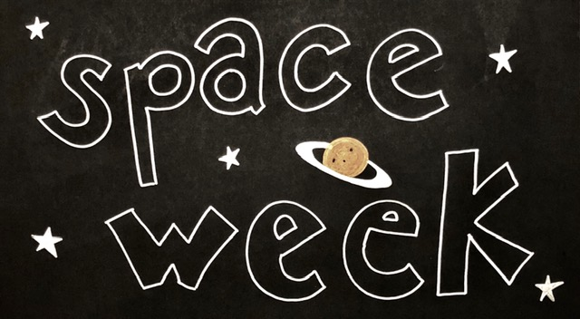 A handwritten sign that says space week, written in silver sharpie on black paper