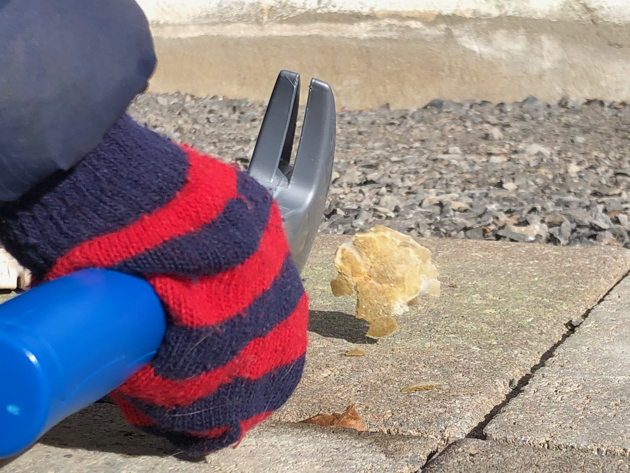 A child's hand wearing a striped red and navy gloves holds a blue and grey plastic hammer. A fabricated moon rock is seen next to it, in motion, after being smashed