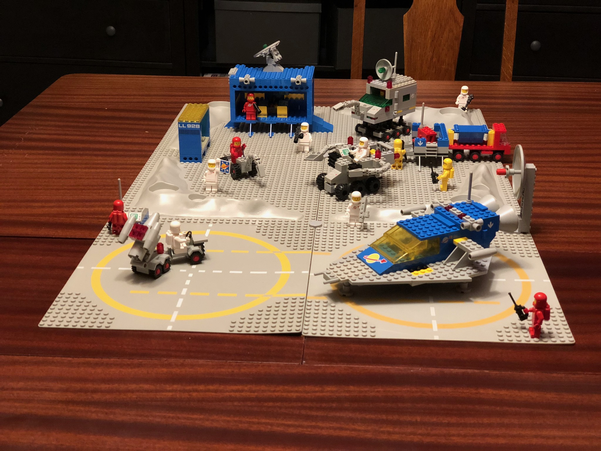 A collection of vintage space lego sets sitting on four grey lego boards, atop a dining table