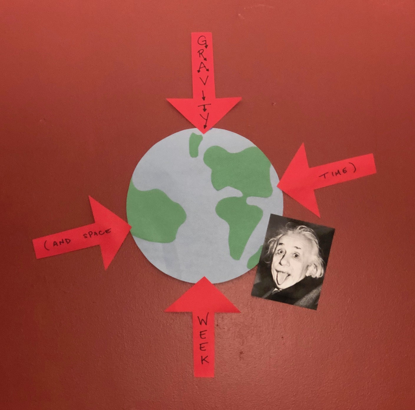 An earth made of construction paper is pasted on a wall. Four red arrows point towards the earth, each with part of the sentence Gravity and Spacetime Week. A picture of Albert Einstein with his tongue out overlaps part of the earth. They are all based on a dark red wall.