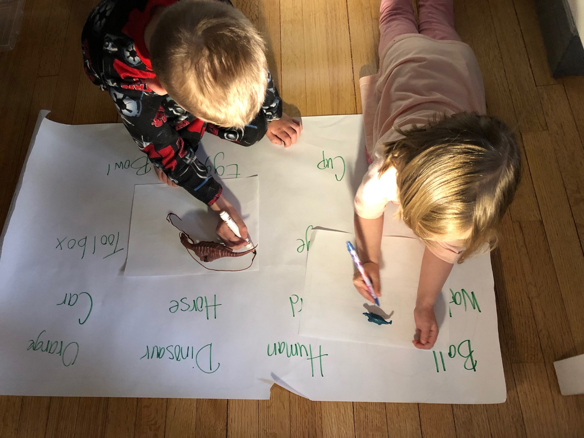 Two young children are seen drawing on white pieces of paper. Each paper has a plastic dinosaur, with a light casting a shadow on the paper.