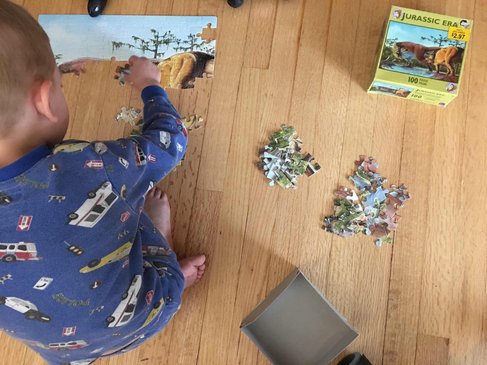 A young boy is putting together a puzzle from the jurassic era. Piles of sorted puzzle pieces sit beside him.