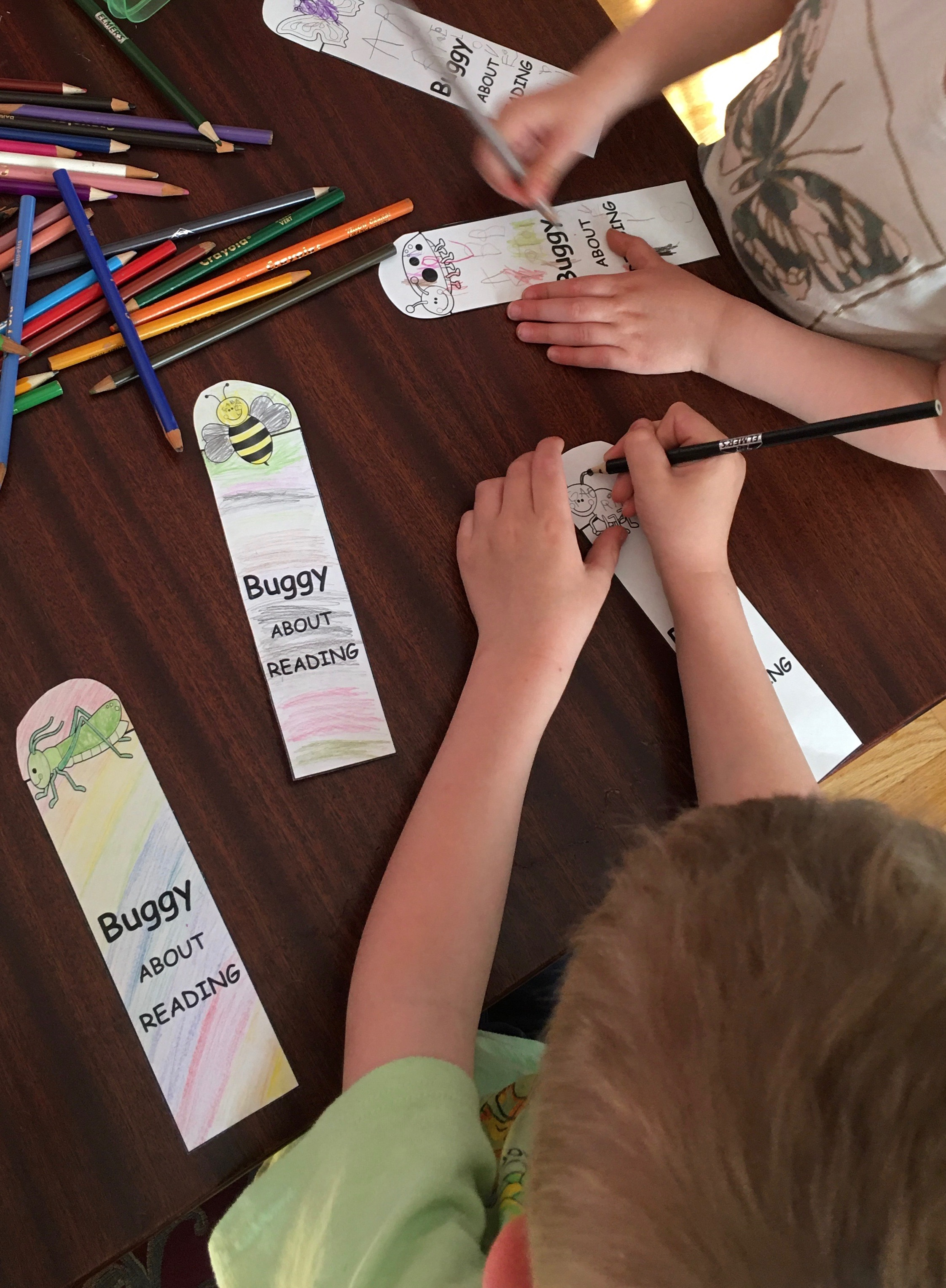 Two children are seeing colouring in paper bookmarks that read Buggy About Reading. Each bookmark has an insect on it.